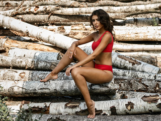 Portrait of a beautiful girl with a tanned body on the background of cut down trees, logs. She is in a red swimsuit in different poses with different emotions.