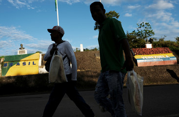 Venezuelan men carry bread loaves to sell to those queued in line at the Pacaraima border control