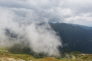 mountain ridge covered by half with the cloud