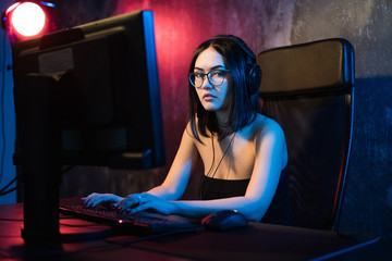 Beautiful young girl wearing glasses and gaming headset plays online game on gaming PC in dark area. Streaming online games on internet