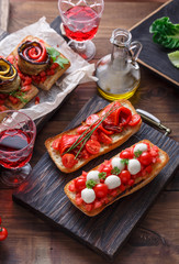 Bruschetta with tomato, basil and mozzarella cheese on wooden board. Traditional italian appetizer or snack, antipasto