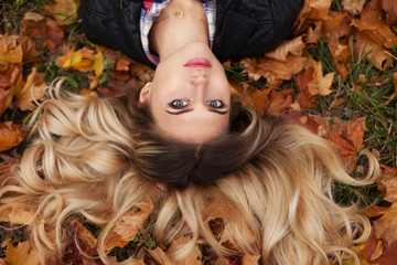 Portrait of beautiful cute blonde young woman. Posing on golden autumn nature background. Fashion photo