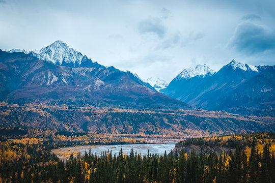 Glenn highway. Matanuska river, mountains covered with a snow, autumn trees. Alaska.