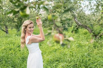 elegant woman in green garden with apple trees