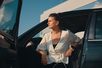 Confident woman getting down from car
