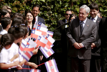 Chile's President Sebastian Pinera greets children during a welcoming ceremony at the Presidential house in San Jose