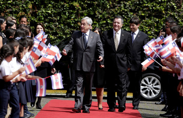 Chile's President Sebastian Pinera walks next to Minister of Foreign Affairs Roberto Ampuero, during a welcoming ceremony at the Presidential house in San Jose