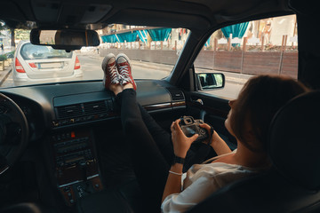 Modern woman tourist, photographer relaxing in the car holding a