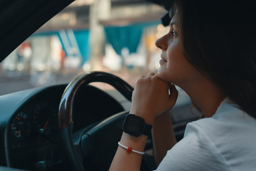 Close-up preety woman portrait holding hands on the steering whe