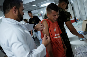 Venezuelan boy receives a free vaccination given by a volunteer after showing his passport at the Pacaraima border control