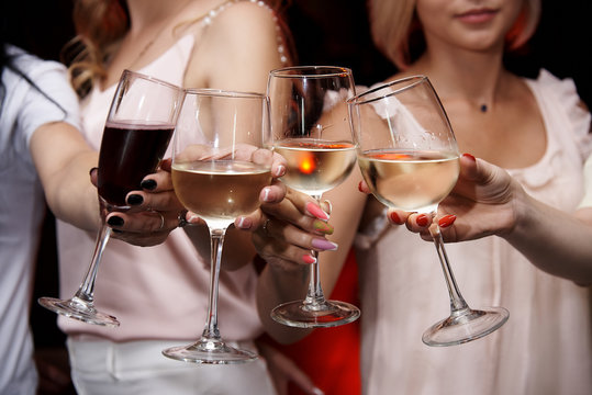 Сlinking glasses of cold wine in female hands.