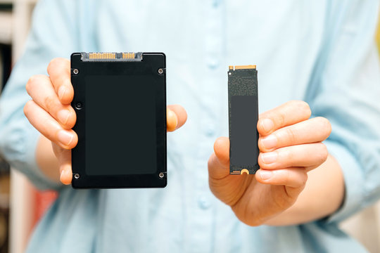 Woman hands holding new NVME PCIE SSD hard drive disk with high read and write speed comparing to SSD solid state drive