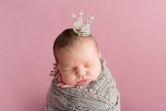 Sleeping newborn girl on a pink background. Little princess with crown. Photoshoot for the newborn. 7 days from birth. A portrait of a beautiful, seven day old, newborn baby girl