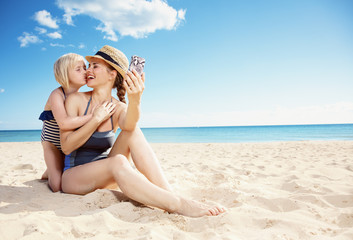 mother and daughter taking selfie with smartphone while kissing