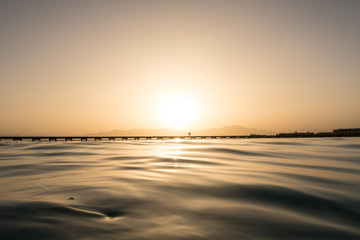 Silhouette of people walking on a jetty in the Sunset from a natural pool on the reef top in the Red Sea, Egypt