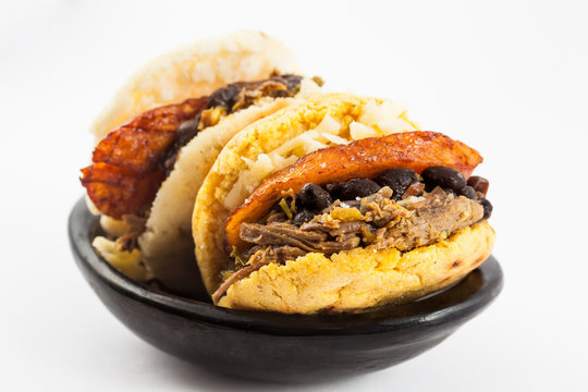 Arepas filled with shredded beef, black beans, plantain and cheese served in a black ceramic dish on white background