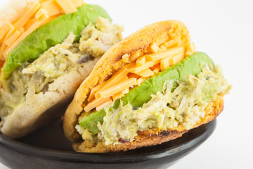 Arepas filled with shredded chicken and avocado served in a black ceramic dish on white background