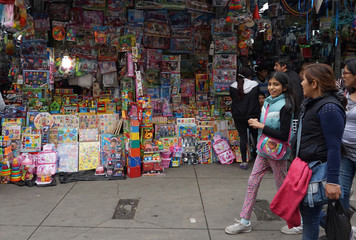 People walk past a stand that sells toys and other products imported from China at Central Market in Lima