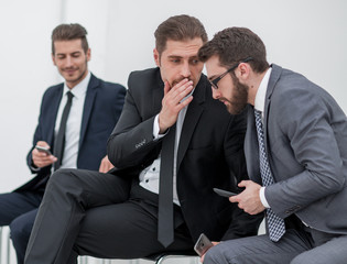 employees discuss the news, sitting in the office hallway