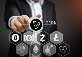 Business man points his finger at  TRON coin icon  among others Cryptocurrency on Virtual Touch Screen , Conceptual