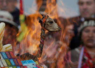"A fetus of llama burns as part of an offering during the inauguration of the new Bolivia's presidential palace named ""La Casa Grande del Pueblo"" in La Paz"