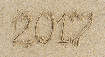 2017 write on sand on the beach at the day. Happy old year.
