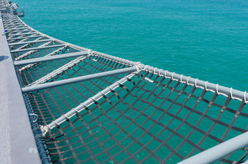 A mesh of battleship on blue sea background .A mesh is a barrier made of connected strands of metal, fiber, or other flexible or ductile materials.
