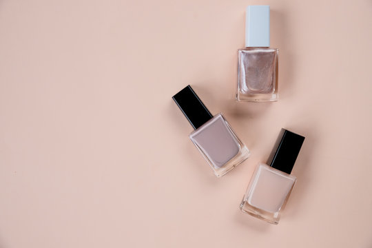 Creative flat lay of fashion bright nail polishes on a beige background. Minimal style. Copy space. Beauty blogger concept. Top view. Nude tones.