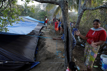 A group of villagers set up a temporary shelter at a refugee camp after an earthquake hit Sigar Penjalin village in North Lombok