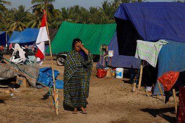 A woman walks at a refugee camp after an earthquake hit Sigar Penjalin village in North Lombok