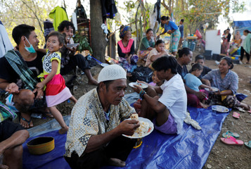 A group of villagers take their breakfast at a refugee camp after an earthquake hit Sigar Penjalin village in North Lombok