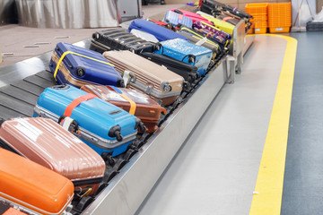 Bright suitcases and bags on luggage conveyor belt in airport