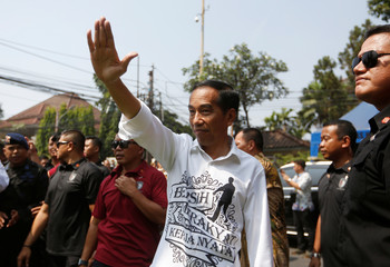 Indonesian President Joko Widodo waves to supporters after registering himself and his running mate Islamic cleric Ma'ruf Amin for the 2019 presidential election at the General Election Commission in Jakarta