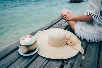 Women wear a sea hat she is happy and sitting, coconut drink on the wood bridge and look to beach seaside, cloud and blue sky is endless background, copy space.