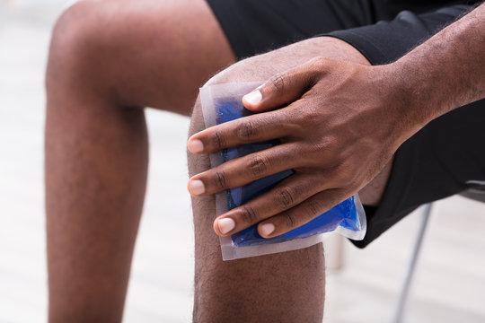Man Applying Ice Gel Pack On His Knee