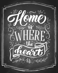 Home is where the heart is hand drawn lettering on black chalkboard background. Vector vintage illustration.