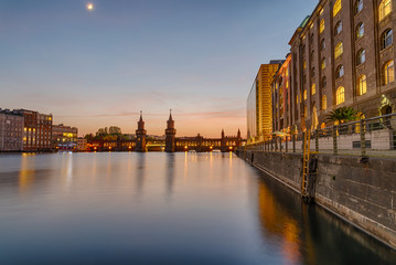 The banks of the river Spree in Berlin with the Oberbaum Bridge in the back after sunset