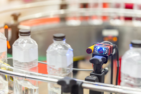Microscan, MicroHAWK and MicroVISION includes the barcode reading technology for the production line of plastic bottles on a conveyor belt in mineral water factory.