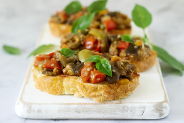 Bruschetta with caponata or ratatouille from various vegetables on a light background.