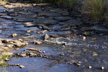 ein fast ausgetrockneter Fluss mit kleinen Stromschnellen