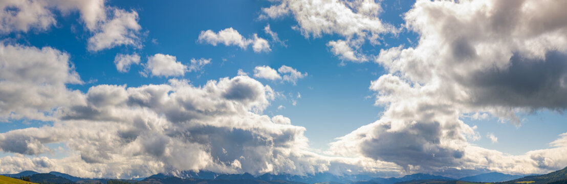 panorama of a gorgeous cloudscape above the mountain ridge. beautiful natural background of autumn sky