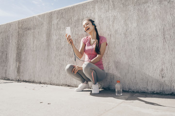 cheerful slim girl sitting on the ground listening to music on headphones and relaxing after workout
