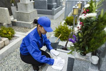 お墓の掃除をする作業服の女性