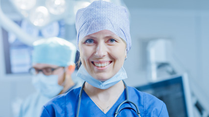 Portrait of the Professional Nurse / Medical Assistant Removed Surgical Mask after Successful Operation. In the Background Modern Hospital Operating Room.