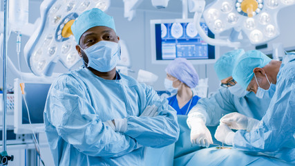 Diverse Team of Professional Surgeons Performing Invasive Surgery on a Patient in the Hospital Operating Room. Surgeons Use  and other Instruments.