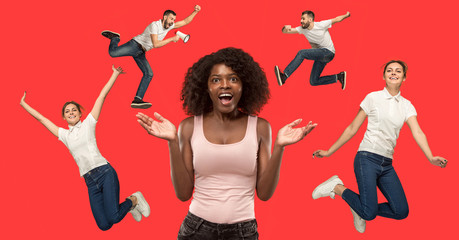 Wow. Beautiful female half-length portrait isolated on red studio backgroud. Young surprised woman and jumping running man isolated on red. Human emotions, facial expression concept. Trendy colors