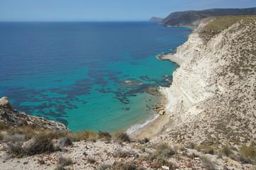 Coastal sandstone cliff and clear water of the Mediterranean sea near Agua Amarga, Cabo de Gata-Nijar Natural Park, Almeria, Andalusia, Spain