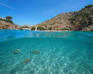 Spain Javea Cala Granadella beach with fish and sand underwater, split view above and below water surface, Mediterranean sea, Costa Blanca, Alicante, Valencia