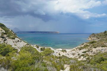 Spain Javea bay, Cala Sardinera with stormy sky and the cape San Antonio in background, Mediterranean sea, Costa Blanca, Alicante, Valencia