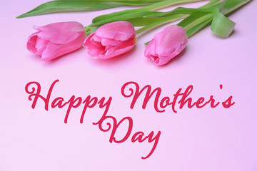 Beautiful tulips and greeting Happy Mother's Day on color background